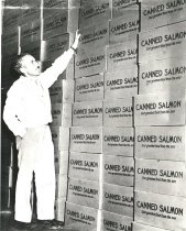 Image of Tony Mastacich with stacks of canned salmon