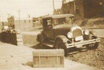 Image of Old car, crate on sidewalk