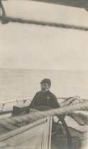 Image of Unknown man at helm of sailing vessel