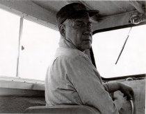 Image of Arnold Klingman steering boat