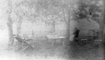 Image of 2012.043.025-.026 - Unknown woman sitting in a chair outside under the trees
