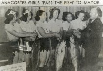 Image of Marineers Pageant girls pass fish to mayor
