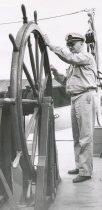 Image of Captain (?) using stern steering wheel