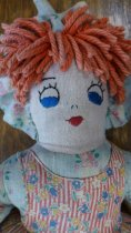 Image of Detail of face of handmade cloth and yarn doll