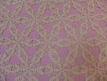 Image of Detail of crocheted bed spread with pink sheet