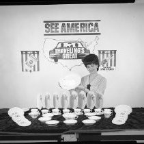 Image of AC Sparkplug - 65-15462) Eighteen black and white film negative images and one color negative image of Bray with dishes on table; blank screen behind her without posters  1, 4, 6-8, 10, 13, 15-17) Bray wearing a printed blouse and holding plates;  AC Oil Filter, See America Traveling Great, and Fire-Ring Spark Plug posters on wall in background  2, 3, 5, 9, 11, 12, 14) Bray wearing a sleeveless white shirt and holding plate; d  19) Color negative image of Bray in white button-down blouse holding dish; display in front on table; three AC Sparkplugs posters hung on wall behind her