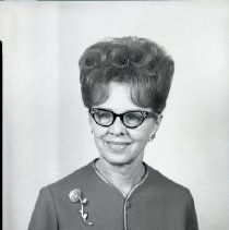 Image of AC Sparkplug - 65-15759) Two black and white negative film images of AC Sparkplugs retiree Clara V. Mohl  1) Mohl  wearing black cats-eye glasses, a bouffant hairstyle, and a button-up coat with white trim; flower brooch on right shoulder  2) Mohl (on right) shown shaking hands with an unidentified man in a plaid wool suit coat, dark tie, and white dress shirt; large aerial view of AC Sparkplugs plant complex in background