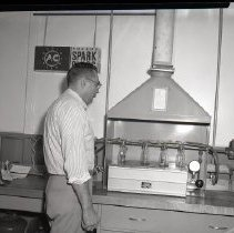Image of AC Sparkplug - 65-15784) Nine black and white negative film images of the tank units press room  1) Man in plaid shirt and light colored pants standing in front of machine; AC Sparkplugs clock on wall on left 2) Main tank unit office with desks; cabinets and fan on wall in background 3) Quality Control board from tank unit assembly plant Division 60, Department 44 4) Woman in dark dress and with bouffant hairstyle wearing white gloves and polishing a black instrument console at work station 5) Man in plaid shirt operating machinery in tank unit plant 6) Woman in sleeveless lightly colored top shown seated from behind and wearing white gloves while working at plant station 7) Man shown from behind in white undershirt in front of large metal machine in plant 8) Man shown partially on right operating large machine with his hand on control on right 9) Desk in office with large corkboard display of console covers, hub cap in upper left corner, and vertically hung speedometer unit cover on right