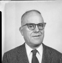 Image of AC Sparkplug - 65-15973) Four black and white negative film images of AC Sparkplugs retiree John H. Oliver  1) Oliver shown in a patterned dark suit, tie, white dress shirt, and glasses 2) Oliver (on right) shown shaking hands with taller man in white dress shirt (name embroidered on breast but not legible in image) in front of aerial photograph of AC Sparkplugs plant complex