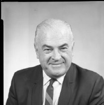 Image of AC Sparkplug - 66-16013) Two black and white negative film images of Harry D. Rothman in a dark suit, diagonally striped tie with tie chain, white dress shirt; hair is white and slicked back; name printed on white pocket square in left breast coat pocket