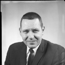 Image of AC Sparkplug - 66-16017) Two black and white negative film images of Jack E. Hill  in a dark suit,black tie, and white dress shirt; name written on white pocket square in breast pocket