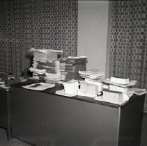 Image of AC Sparkplug - 66-16084) Two black and white negative film images of key punch work tables  1) Desk with papers piled on top of it; two patterned curtains in background 2) Back view of women seated at desks working