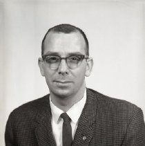 Image of AC Sparkplug - 66-16113) Two black and white negative film images of Douglas J. Ayers in a dark checkered suit coat, dark tie, white dress shirt, and glasses; white name card with printed name along bottom edge of photograph