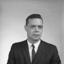 Image of AC Sparkplug - 66-16369) Two black and white negative film images of John Tuttle in a black suit coat, tie, and white dress shirt; holding white name card along bottom edge of photograph in right hand
