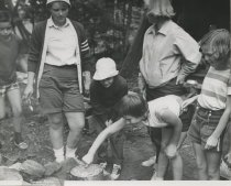 Image of Girls Stirring Pot Over Campfire - Print, Photographic