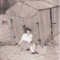 Image of A2011.039.S03.F02.018 - Elizabeth Hillmer seated on sand next to wood shed