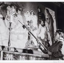 "Image of Hunter, George - All Saints Anglican Church with altar boy John Steward Vehos using a taper to light altar candles-famous painting, ""Our Virgin of the Snows"" in background, Aklavik, 1952 GH No. 3341"