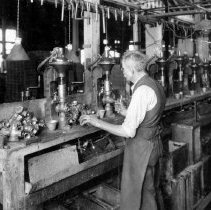 """Image of Photo from booklet """" The Story of Faucets """"  old employee in factory"""