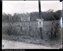 "Image of Glass negative of signs on Dandy Trail, Indianapolis, Indiana, ca. 1930s - Undated glass negative of signs on Dandy Trail in Indianapolis: ""Dandy Trail  / Fisheries / 2000 Ft.,"" ""Sargent Rd.,"" and ""Danger / T / Marion Co. / Highway Dept.""  In the distance are corn shocks in a field."