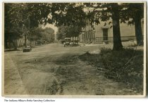 """Image of Photo of River Road, Main Street in Vevay, Indiana, ca. 1920 - A banner for """"Harry Artz- We Serve Moores and Ross Ice Cream"""" and several Coca Cola signs are seen along this dirt street. Both cars and horse carriages are parked along the road and there is a water pump in the middle of the street."""