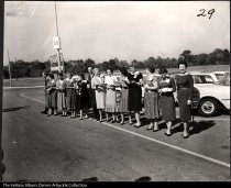 Image of Tupperware managers receiving company cars, Indianapolis, Indiana 1961 - Tupperware branch managers, pose with new cars in the parking lot of Eastgate Center (later Eastgate Consumer Mall). Tupperware presented company cars to managers. The Ford automobiles were provided by Ed Martin Ford. Standing 5th from the right is Goldie Arbuckle and to her left is her husband Robert Arbuckle.