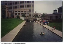 """Image of Central Canal, Indianapolis, Indiana, ca. 2006 - View looking south from W. New York Street at the Central Canal. People ride in paddleboats and gather in tents at the Indiana Historical Society to the right. In the background is the State Office Building. View taken in about 2006 as a """"Now"""" view for image ia-0030-0003."""