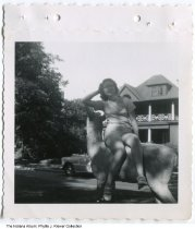 Image of Phyllis Needham sitting on deer sculpture in Woodruff Place, Indianapolis, Indiana, ca. 1951 - One of several snapshots of the roommates of Phyllis (Needham) Riewer. In about 1951 they rented rooms at 828 Middle Drive in Woodruff Place. As young single women, they worked at L. S. Ayres department store and Norway's Sanatorium. This image depicts Phyllis sitting on a deer sculpture.