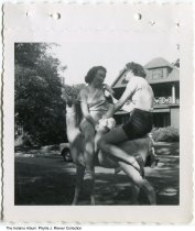 Image of Two women sitting on deer sculpture in Woodruff Place, Indianapolis, Indiana, ca. 1951 - One of several snapshots of the roommates of Phyllis (Needham) Riewer. In about 1951 they rented rooms at 828 Middle Drive in Woodruff Place. As young single women, they worked at L. S. Ayres department store and Norway's Sanatorium. This image shows Phyllis on the left and a friend sitting on a deer sculpture. The friend holds a bottle of Falstaff beer.
