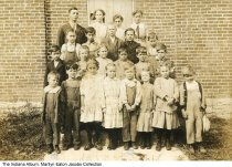 """Image of Students at Shaul School #7, Stony Creek Township, Madison County, Indiana, ca. 1910 - Elementary school students with their teacher in front of a brick school. Written on the back is: """"Shaul School #7 / Corner 53rd & 500 W / Stony Creek Township / Madison Co. Indiana / 1st-8th Grade."""" Also the names """"Harrison[?] & Herbert"""" written in ballpoint pen. The names probably correspond to the two boys in the front with pen circle at their feet. On a Stony Creek Township map, School 7 is located in the northeast corner of Section 31 near property owned by the Shaul family."""