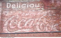 Image of Snapshot of ad on a building at E. 16th Street and College Ave, Indianapolis, Indiana, ca. 2010 - Snapshot showing a painted Coca Cola ad ghost sign on a brick two-story commercial building located on the SW corner of E. 16th Street and College Avenue, just prior to its demolition.