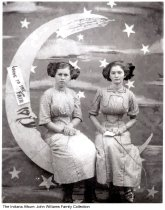"""Image of Two girls pose on a moon prop with a """"Going to the Fair"""" sign, Indiana, ca. 1915 - Two young women wearing large hair bows and Edwardian style dresses posing on a cut-out moon prop with a sky and stars background. A sign on the moon reads """"Going to the Fair."""" This is possibly the Wabash County Fair or the Indiana State Fair. This prop was known as a """"paper moon"""" or """"man on the moon"""" and was popular between 1900 and 1940."""