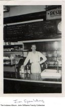 Image of Jim Spaulding working at Wabash bar or restaurant, Wabash, Indiana, ca. 1938 - Photograph of a man identified as Jim Spaulding wearing an apron and working in a bar or restaurant. This is probably a bar owned by ? Williams, possibly the Union Restaurant and Bar.