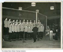 """Image of Photo of Allison's Glee Club, Indianapolis, Indiana, 1964 - Concert photo of Allison's Glee Club [Allison Transmission]. The piano player was nicknamed """"Brownie."""" Luther Steel (b. 1922) is 4th from the left in the back row. The Season's Greetings light shades indicates that it was the Christmas season."""