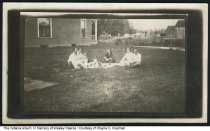"Image of Picnic with Pearce, Lewis, and Griffis families, Williamsburg, Indiana, 7-4-1914 - Six people are seated around a picnic blanket., with a house and barn in the background. The back of the card has a handwritten note reading ""Dr. & Mrs. Paul Lewis, Mr. & Mrs. U. C. (or V. C.) Griffis (left), Omar, Olive, and Reade (right) - Picnic July 4th 1914 Williamsburg."""