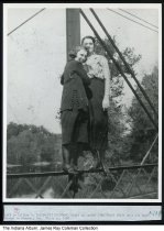 """Image of Women on an iron bridge, Winamac, Indiana, ca. 1925 - A typed caption reads """"Left is Lillian R. (Alderson) Troutman Right is Isabel (Troutman) Weldy on a old iron bridge in Winamac, Ind. Photo ca. 1930."""" Based on the clothing and hair, this is possibly the early 1920s. The Tippecanoe River is in the background."""