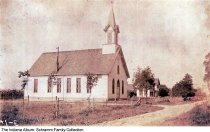 Image of Postcard of German Lutheran Church, New Palestine, Indiana, ca. 1912 - View of a frame church and a two-story house on a dirt road. Identified by the lender as the Evangelical German Lutheran Zion Church in New Palestine.