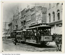 """Image of Photo of an Illinois Street streetcar, Indianapolis, Indiana, ca. 1915 - Photo of a group of men riding on a streetcar marked """"Illinois Street"""" and """"Citizens Street R. R. Co."""".  In the background are signs for Miles Restaurant, China Glass Queensware, and a men's clothing shop. A mule-drawn carriage is behind this three-car streetcar."""
