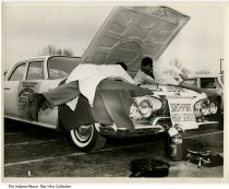 Image of Photo of car mechanics at Southport High School, Indianapolis, Indiana, 1961 - Two young men at work under the hood of a car. The car has a sign on front for Southport High School, and one on the side promoting an event at Arsenal Tech on April 29, 1961.