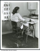 Image of Photo of a woman ironing in a kitchen, Indianapolis, Indiana, ca. 1950 - Posed commercial photograph of a woman seated on a high stool in a kitchen, ironing on an ironing board.