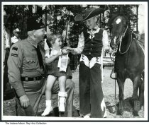 Image of Photo of Sahara Grotto Horse Patrol award, Indianapolis, Indiana, 1962 - Posed commercial photograph of a boy in a cowboy suit handing an award to a girl wearing a leg brace. She is sitting on the lap of a man wearing a fez that seems to read Sahara Grotto Horse Patrol. The award ribbon is marked Sahara Grotto Horse Patrol 1962, First Place.