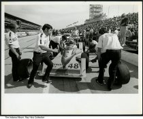 "Image of Photo of racecar in a pitstop at Indianapolis 500, Indianapolis, Indiana, ca. 1975 - Photo of men in the pitcrew working on a racecar in a pitstop at the Indianapolis 500 racetrack. The stands are filled with spectators. The car is marked ""Jorgensen Eagle #48."""