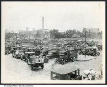 "Image of Photo of the Indianapolis Producers Market, Indianapolis, Indiana, 1933 - Photo showing a group of produce trucks at a market. Some of the truck plates seems to read ""1933."" Signs can be seen for Indianapolis Producers Market, Market Restaurant Beer, Joseph Hollander Lunch, Schmid & Smith Realtors."