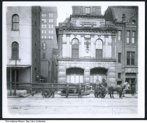 """Image of Central Fire Station #13, Indianapolis, Indiana, 1904 - Photo of the Hook and Ladder Central Fire Station #13 at Capitol Avenue and West Washington Streets. The hook and ladder truck in front is marked """"Aerial Truck No. 1 IFD."""" The Jacob Metzger & Co. office is to the right. Seen in the alley (then known as Mechanic Street and currently named Scioto Street) is a hardware and the Bismarck Cafe.  Central Station moved from this location in 1912."""