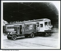 """Image of U. S. Mail truck and interurban railway car, Indianapolis, Indiana, 1935 - A U. S. Mail delivery truck with bundles of mail is parked near an Indiana Railroad interurban in the train shed of Indianapolis Traction Terminal. The mail car is marked """"375 Fort Wayne."""""""