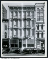 """Image of Oilar Banner Furniture Company, Indianapolis, Indiana, 1918 - Cars parked in front of a building marked """"Erected 1870 - Oilar Banner Furniture Co."""" Furniture for sale is visible in the front window. Signs on adjacent buildings promote  John L. Vesper Tailor and Kipp Bros. Company, fancy goods and importers (37 South Meridian Street)."""