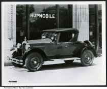 Image of 1923 Hupmobile, Indianapolis, Indiana, 1924 - Photo of an automobile identified on the back as a 1923 Hupmobile. It is parked outside a building with the car name and logo on the windows. A note on back states that the dealership was on North Meridian Street, and that the car cost $12,000.  