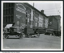 Image of Photo of Maryland and Meridian Streets, Indianapolis, Indiana, 1921 - Photo of the corner of East Maryland and South Meridian Streets looking east. M. O'Connor and Company's  Wholesale Grocers was on the northeast corner. Murals painted on the side advertise Hoosier Poet Foods (with a portrait of James Whitcomb Riley), Pillsbury's Best flour, Blue Valley Butter, Lincoln Highway cigars, and Camel cigarettes. Trucks from the Indianapolis Printing Company, Merchants Heat and Light, and several streetcars are in the foreground. Buildings in the distance are the Jacob Metzger Company bottling works, the Century Building, and the Majestic Building.