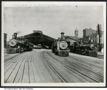 Image of Photo of east end of the train shed, Indianapolis, Indiana, ca. 1920 - Train workers and locomotives in what is identified on the photo as the east end of the train shed. Also seen are signs for a wholesale millinery store, and the Bee Hive box factory.