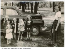 Image of Children at Riverside Park, Indianapolis, Indiana, ca. 1950 - Snapshot of siblings and cousins posing in front of a car in Riverside Park, ca. 1950. Identified as (left to right): Barbara Karn, Pamela Perry, Karen Karn, Sharon Perry, Mary Jo Karn, and adult Mary (Powers) Karn.