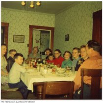 "Image of Sunday dinner at Grandma Lillie Castor's house, Madison County, Indiana, ca. 1955 - Color snapshot of family members at the dining room table. Identified on the back as ""Sunday dinner at Grandma's / Free Rd east of St. Rd 9N on 3."" Clockwise from left: Kent Sims, Esther Sims, David Lawler, mothr Lillie Castor, Nancy Lawler, Dana Sims, Danny Lawler, Sharon Sims, Lucretia Lawler, Elna Mae (Castor) Lawler, Chaud [?] Lawler (back of head)."